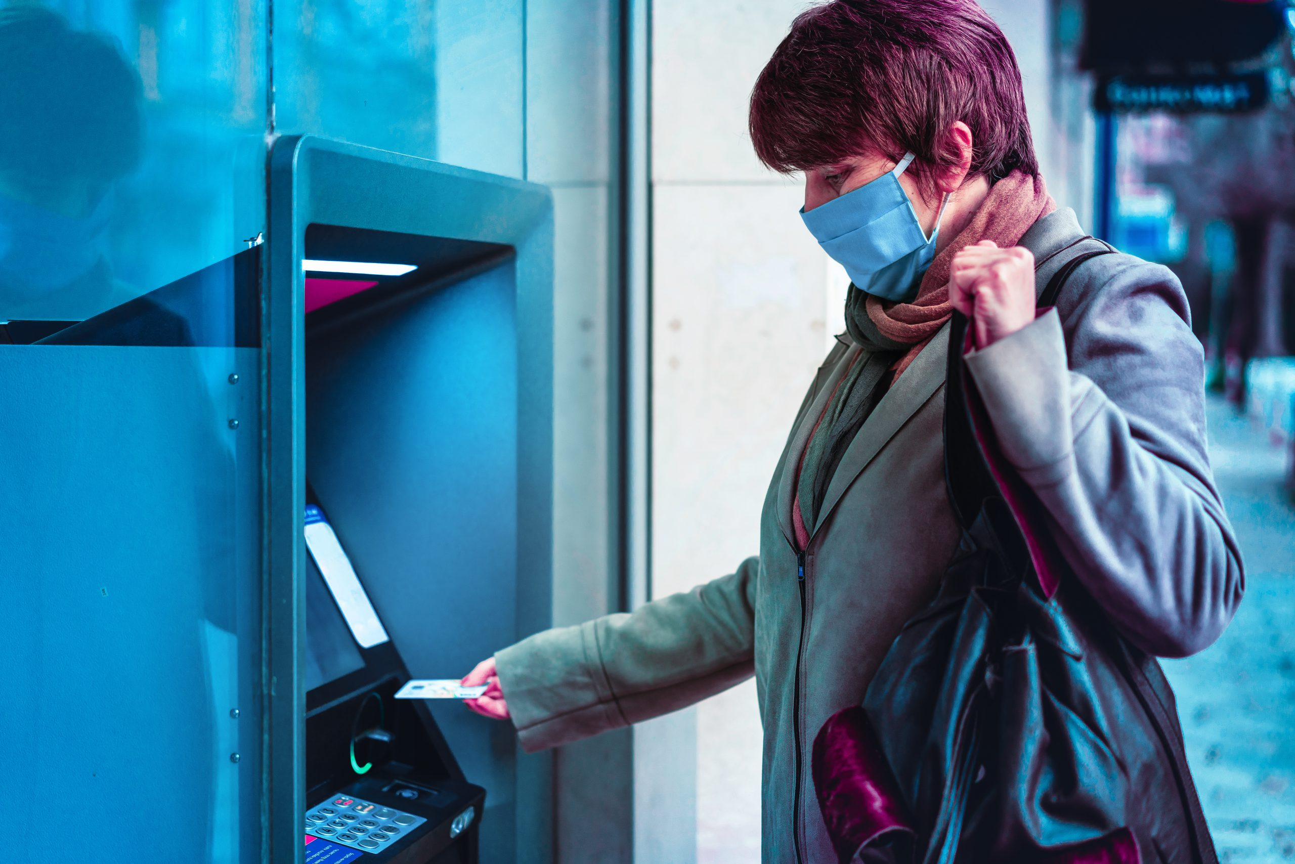Woman with protective mask standing on city street and using ATM machine.